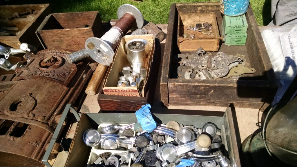 Flea market vendor booth with boxes of old doorknobs and other hardware