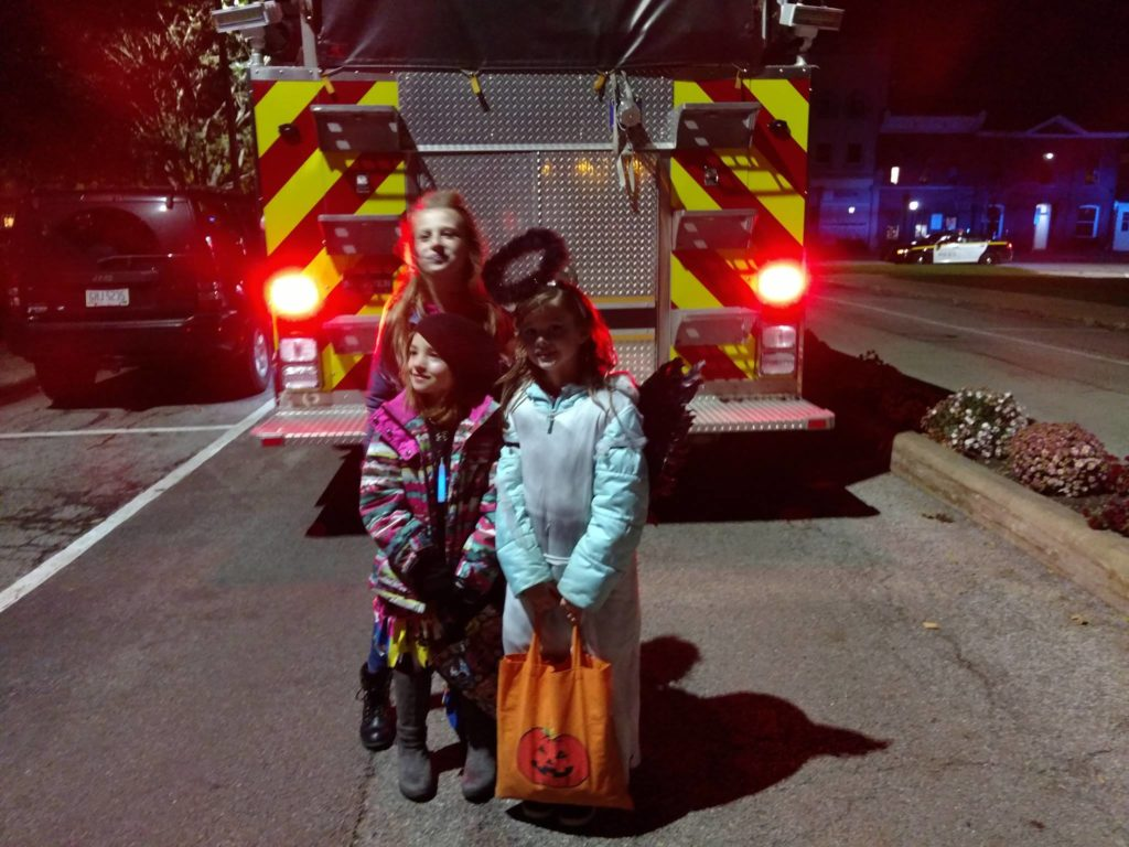 Two kids behind a fire truck waiting for the parade to start