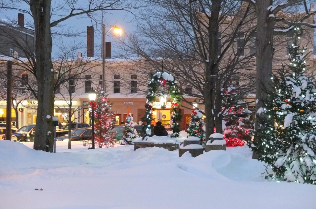 Wide view of snow covered square with Christmas lights and storefronts