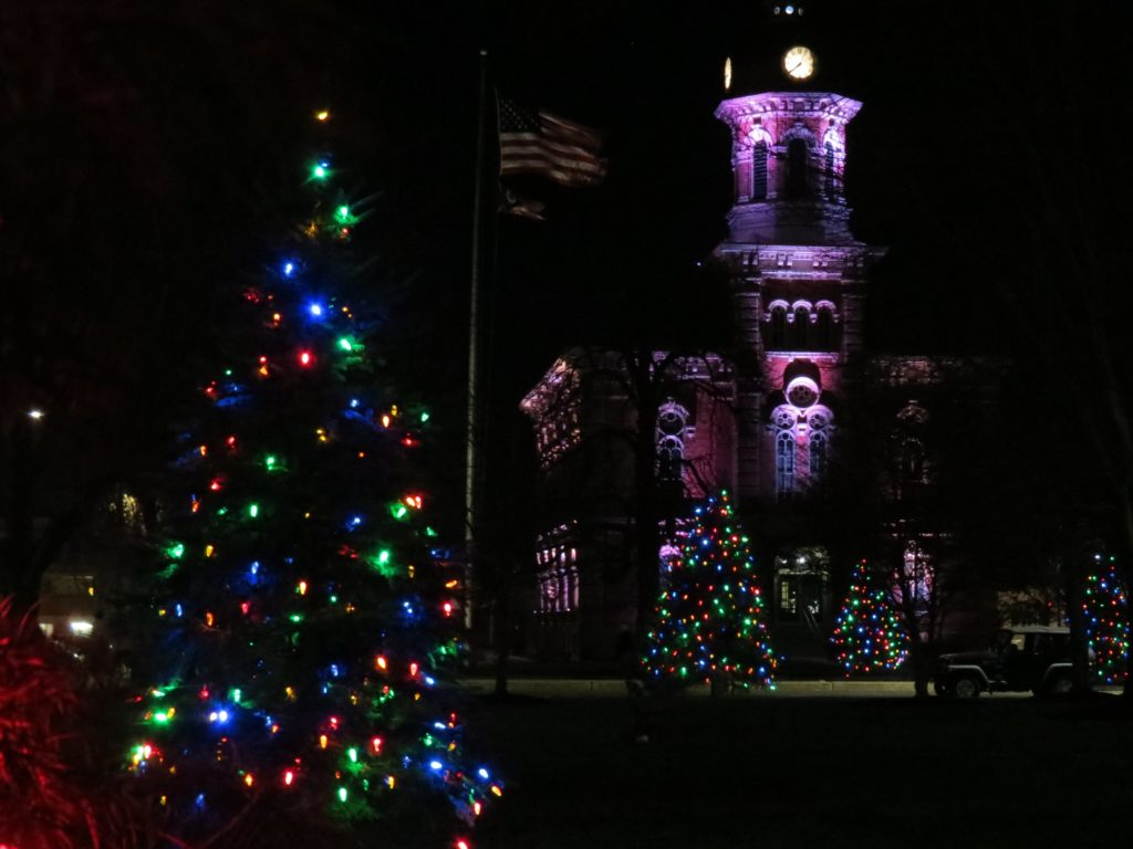 Christmas tree with colored lights and the courthouse in the background